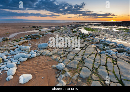 Sunset over rocks of Dunraven Bay, Southerndown, Wales - Stock Photo