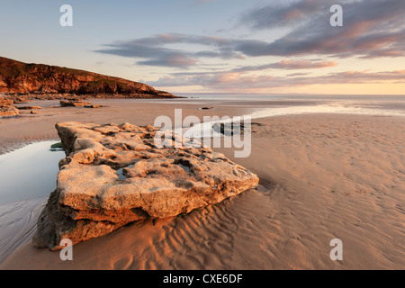 Sunset over rocks with flowing water at Dunraven Bay, Southerndown, Wales - Stock Photo
