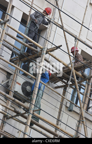 Shanghai, construction workers on a Bambusgeruest - Stock Photo