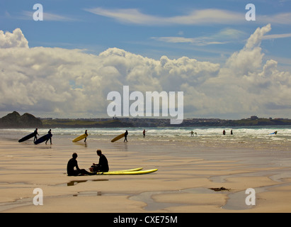 Surfers with boards on Perranporth beach, Cornwall, England - Stock Photo
