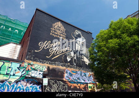 Mural and graffiti on the wall of Henri Henri, a store selling hats since 1932 in Montreal, province of Quebec, - Stock Photo