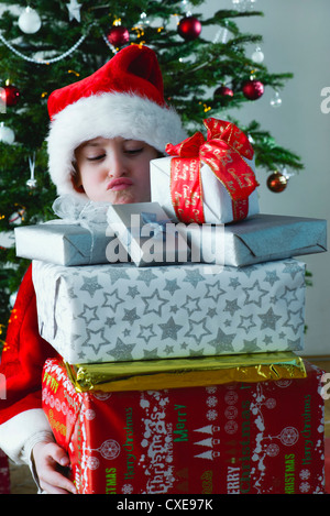 Boy holding stack of Christmas presents with sulky expression on face - Stock Photo