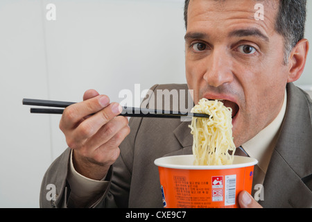 Mature businessman eating ramen noodles - Stock Photo