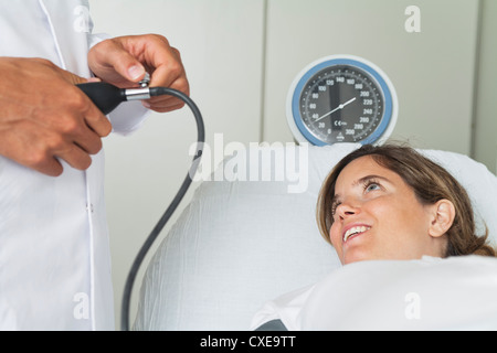 Young woman lying on examination table while doctor checks her blood pressure - Stock Photo