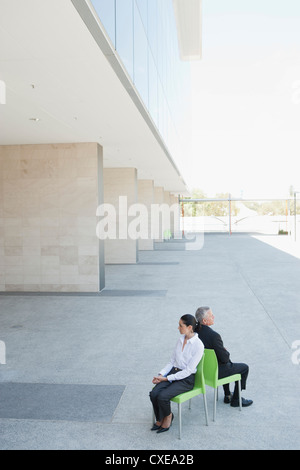 Businessman and businesswoman sitting back to back in chairs outside office building - Stock Photo