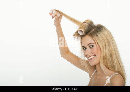 Teen girl rolling her hair with curlers - Stock Photo