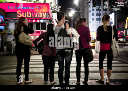 NEW YORK CITY - SEPT 13:  New York City pedestrians waiting at crosswalk in midtown at night - Stock Photo