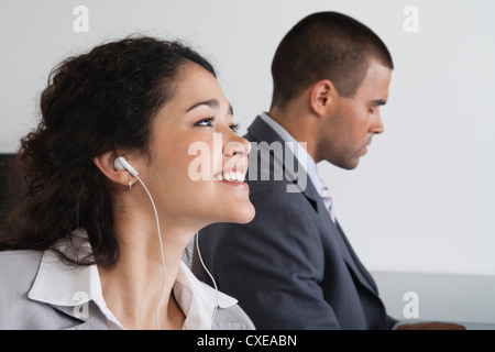 Woman listening to earphones and daydreaming in office - Stock Photo