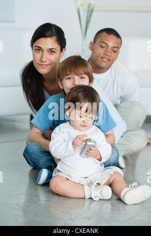 Mother and children sitting on floor at home - Stock Photo