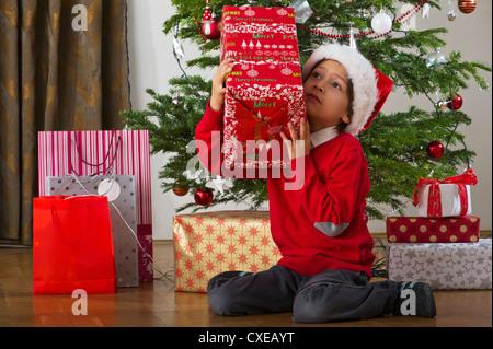 Boy sitting beside Christmas tree, shaking gift - Stock Photo