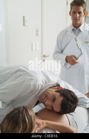 Doctor with ear against pregnant woman's abdomen
