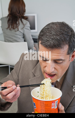 Businessman eating ramen noodles in office - Stock Photo