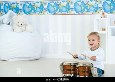 Baby boy playing drums in nursery - Stock Photo