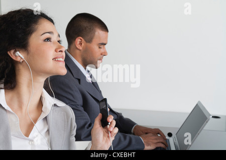 Young woman listening to MP3 player in office - Stock Photo