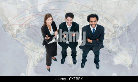 Executives standing on world map - Stock Photo
