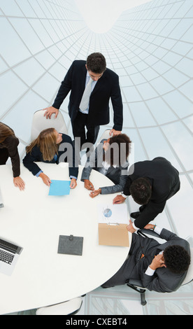 Business associates in meeting on top of superimposed skyscraper image - Stock Photo
