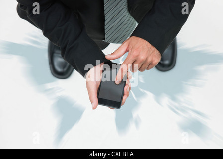 Businessman standing on world map, using smartphone, cropped - Stock Photo