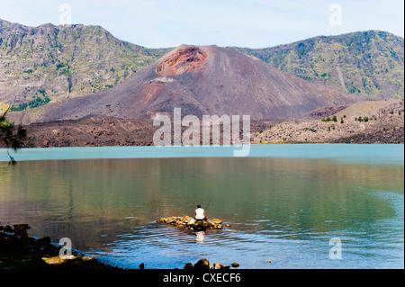 Man fishing in front of Mount Baru Jari, Segara Anak Lake at the bottom of Mount Rinjani volcano crater, Lombok, - Stock Photo