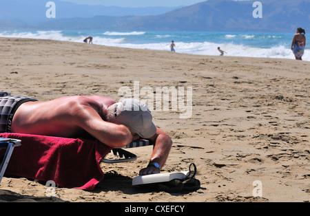Sunbather reading a book from his lounger on Paralia  Kouma beach -West of Rethymnon ,  Crete - Stock Photo