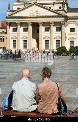 An elderly couple sitting on a bench and looking at the French Cathedral in the Gendarmenmarkt in Berlin, Germany - Stock Photo