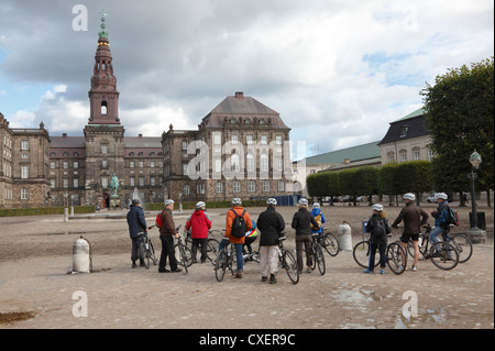 Tourists on a guided bicycle tour at Christiansborg Castle one late summer / autumn afternoon. Copenhagen, Denmark. - Stock Photo