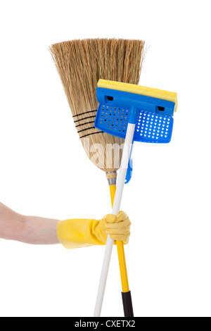 Yellow Rubber gloved hand holding a straw broom and a sponge mop on a white background - Stock Photo