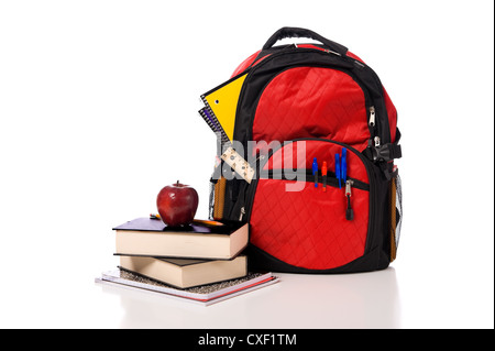 Colorful school back pack overflowing with school supplies including pens, pencils. tablets, notebooks, and books - Stock Photo