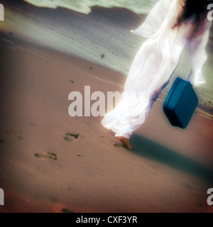 a girl in a white dress at the sea with a suitcase - Stock Photo