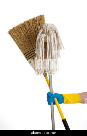 Rubber gloved hand holding a straw broom and a string mop - Stock Photo