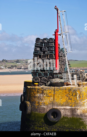 Lobster pots piled high on the quayside at Padstow in Cornwall. - Stock Photo