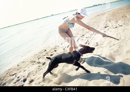 Woman in vacation playing with her dog at the summer beach. Artistic colors added - Stock Photo