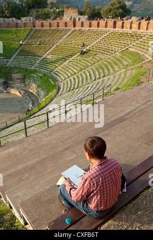 man drawing Teatro Greco Taormina Sicily Italy - Stock Photo
