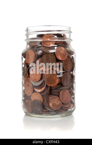 Clear glass jar full of coins on a white background - Stock Photo