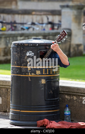 Guitarist in litter bin near King's College in Cambridge - Stock Photo