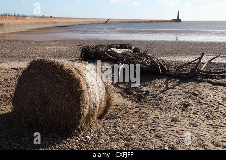 Driftwood and hay bale on Roker beach following stormy weather, north east England, UK - Stock Photo