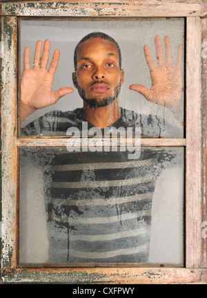 African American man looking out old grunge window - Stock Photo