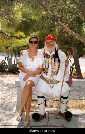 A Greek man in traditional costume posing with a tourist under the Acropolis in Athens, Greece - Stock Photo