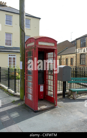 Vandalized public telephone kiosk or box with broken window and missing door - Stock Photo