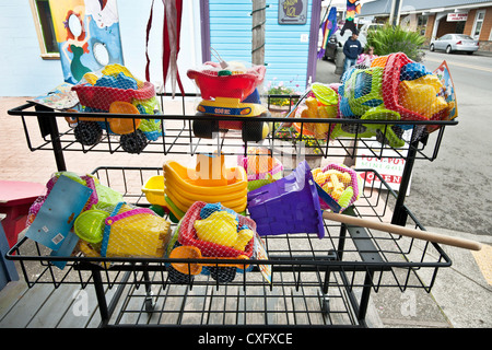 bundled brightly colored plastic beach toys displayed for sale on main street of seaside family resort of Long Beach - Stock Photo
