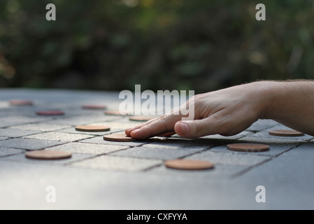 A hand moving a checker piece on a large outdoor checker board. - Stock Photo