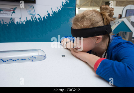 Intech Science Centre child wearing headband to detect Alpha brainwaves during a mindball game sciences education - Stock Photo