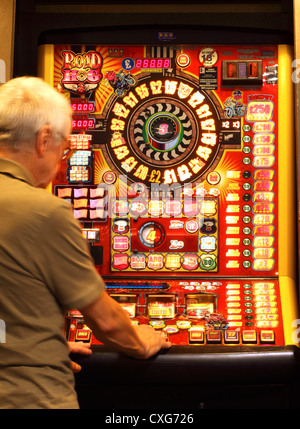 A man approximately 60 years old , (showing slight movement) playing on a slot machine - Stock Photo
