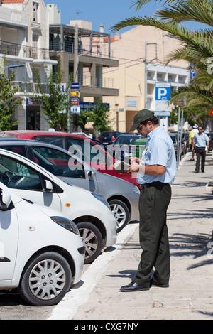 Traffic warden issuing parking ticket to 'Rental Car'. Argostoli Cephalonia Greece - Stock Photo
