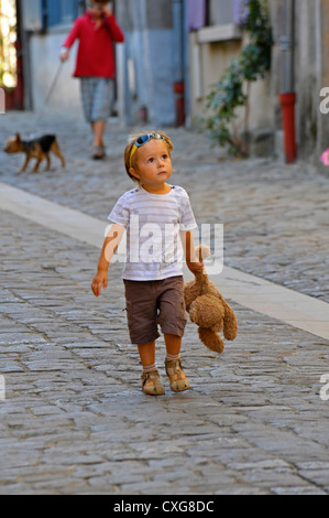 Young boy walking in street clutching a cuddly toy. - Stock Photo