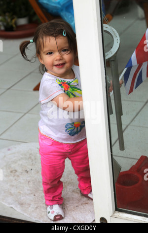 Eighteen Month Old Child Smiling Standing By Conservatory Door England - Stock Photo