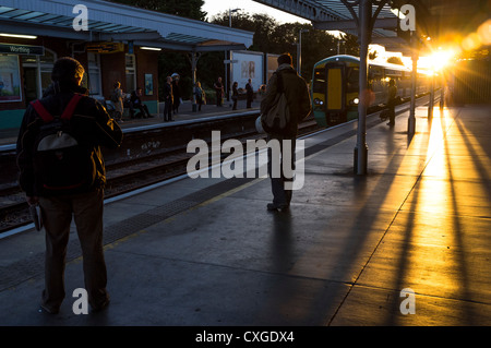 Commuters wait for a train in the early morning sun - Stock Photo