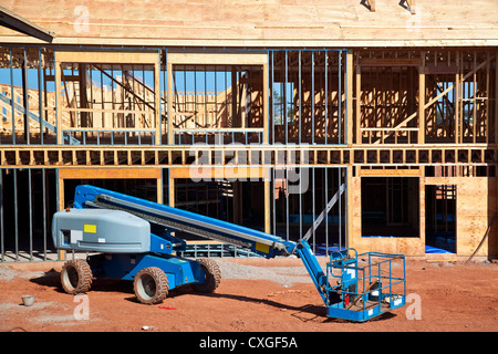 A boom lift with a telescopic arm on a construction site. - Stock Photo