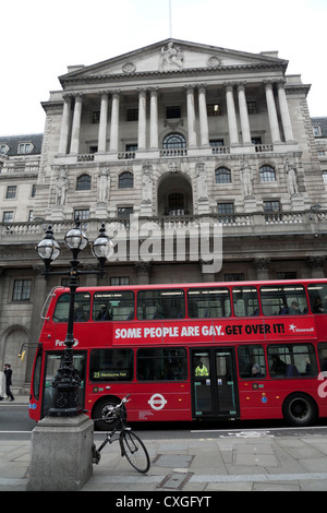 A red double decker bus passing the Bank of England bearing the slogan Some People Are Gay Get Over IT London England - Stock Photo