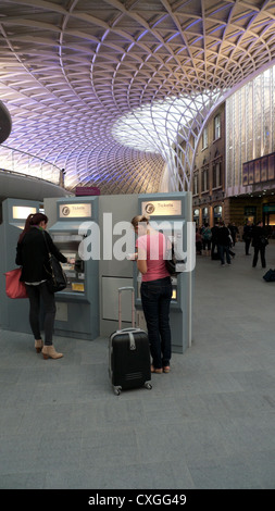People buying train tickets inside King's Cross Train Station concourse ticket hall London England UK - Stock Photo