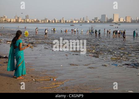 Lady in a sari holding a windmill & looks towards the sea from Chowpatty Beach, Mumbai, India. - Stock Photo